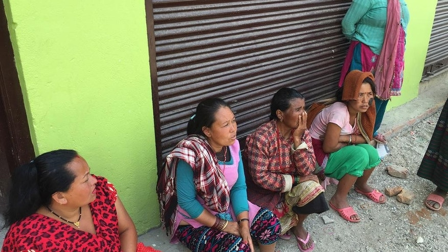In this May 5, 2015, photo, Renu Maya Tsing, second from left, is seated outside of a shop near the town of Sakhu, Nepal. The youth exodus, described by villagers around Nepal as a painful choice between staying with family in their impoverished hometowns or venturing into an often harsh world to make much-needed money, began well before the 7.8 magnitude April 25 earthquake knocked flat whole villages. (AP Photo/Foster Klug)