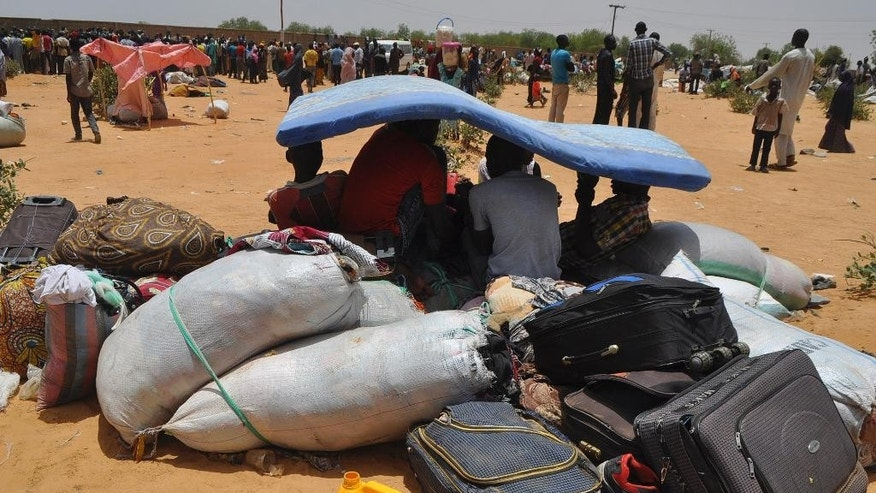 Nigeria refugees shelter under a mattress after they were deported by Niger troops arrive in Gaidam, Nigeria Thursday, May 6, 2015. Niger troops have deported more than 3,000 Nigerian fishermen and refugees escaping Boko Haram, forcing them to undertake a brutal three-day trek in which at least a dozen people died, an official and witnesses said Wednesday. Nigeria's National Emergency Management Agency's Charles Otegbabe said it was alerted by Niger and sent trucks to collect the exhausted refugees at the border, registering at least 3,000 new arrivals in Gaidam town and expect hundreds more. (AP Photo/Jossy Ola)