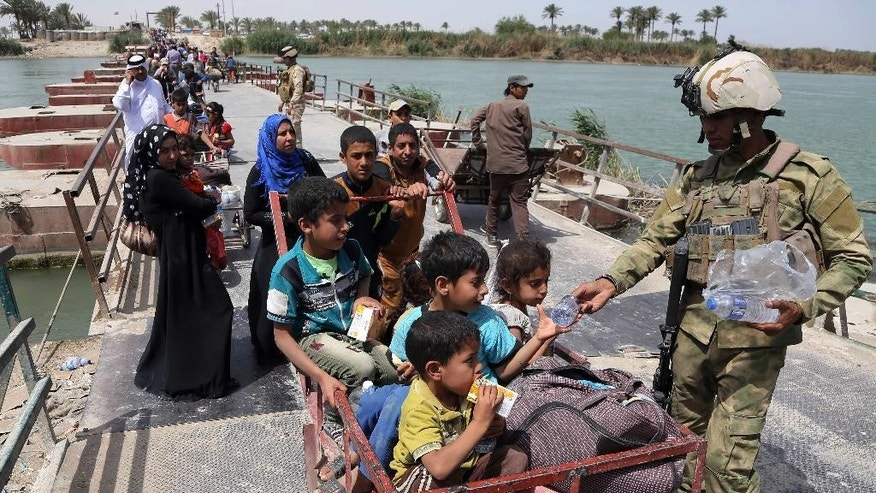 FILE - In this Saturday, April 18, 2015, file photo, Iraq security troops distribute bottles of water to displaced families from Ramadi on Bzebiz bridge 65 km west of Baghdad, Iraq. A Norwegian humanitarian group report says a record 38 million people have been internally displaced in their countries worldwide, with 2.2 million Iraqis alone fleeing in 2014 after the Islamic State group seized their areas. (AP Photo/Karim Kadim, File)