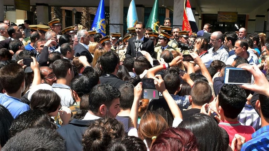 """In this photo released by the Syrian official news agency SANA, Syrian President Bashar Assad, center background, speaks during a public appearance at a school in Damascus, Syria, Wednesday, May 6, 2015. Syrian President Bashar Assad acknowledged on Wednesday what he said were recent """"setbacks"""" in the war against rebels trying to topple him, promising a comeback by his troops entangled in heavy fighting with rebels in northern Syria.  (SANA via AP)"""
