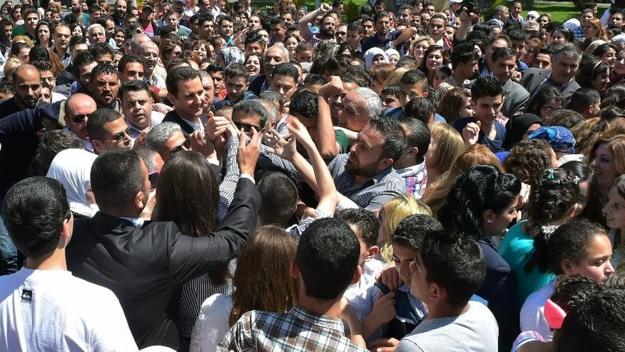 """In this photo released by the Syrian official news agency SANA, Syrian President Bashar Assad, left center, shakes hands with students during a public appearance at a school in Damascus, Syria, Wednesday, May 6, 2015. Syrian President Bashar Assad acknowledged on Wednesday what he said were recent """"setbacks"""" in the war against rebels trying to topple him, promising a comeback by his troops entangled in heavy fighting with rebels in northern Syria. (SANA via AP)"""