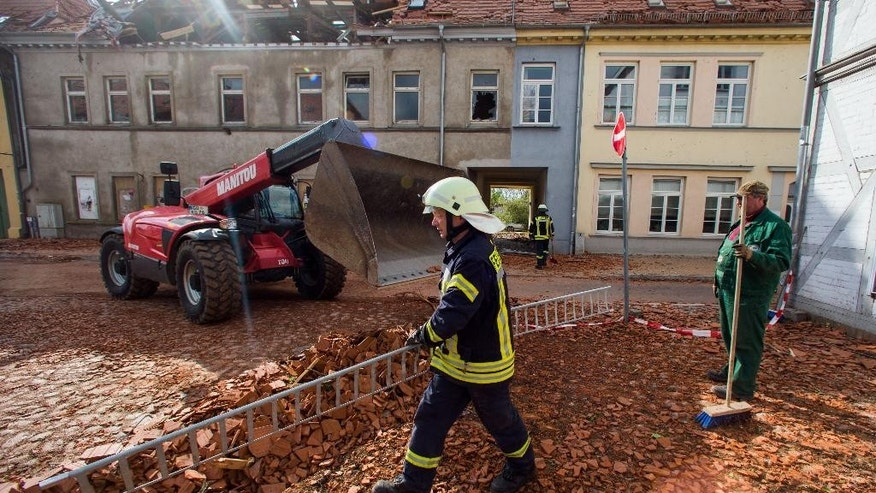 Fire fighters and helpers clear debris a day after a heavy storm hit the town of Buetzow, northeastern Germany, Wednesday, May 6, 2015. A heavy storm caused substantial damage in northern Germany. (Jens Buettner/dpa via AP)