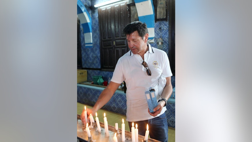 French Jew Jean-luc Ben Ayoub lights a candle at the Ghriba synagogue in Djerba, south Tunisia, Wednesday, May 6, 2015.  Pilgrims arrived for the pilgrimage at Tunisia's Ghriba synagogue, the oldest in Africa.  On April 11, 2002 a deadly attack on the synagogue killed 21 people, including 14 German tourists. (AP Photo/Mohsen May)