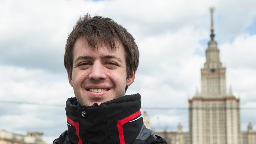 In this photo taken Thursday, April 23, 2015, Nikolai Podchasov, a student at the Lomonosov Moscow State University, poses for a photo in front of the university during his interview with Associated Press in Moscow, Russia. Podchasov, who is due to graduate from the Moscow State University this month, enjoys the lavish celebrations of the Victory Day that Russia marks on May 9 and views it as the ultimate patriotic message of the sacrifice for one's country. (AP Photo/Pavel Golovkin)