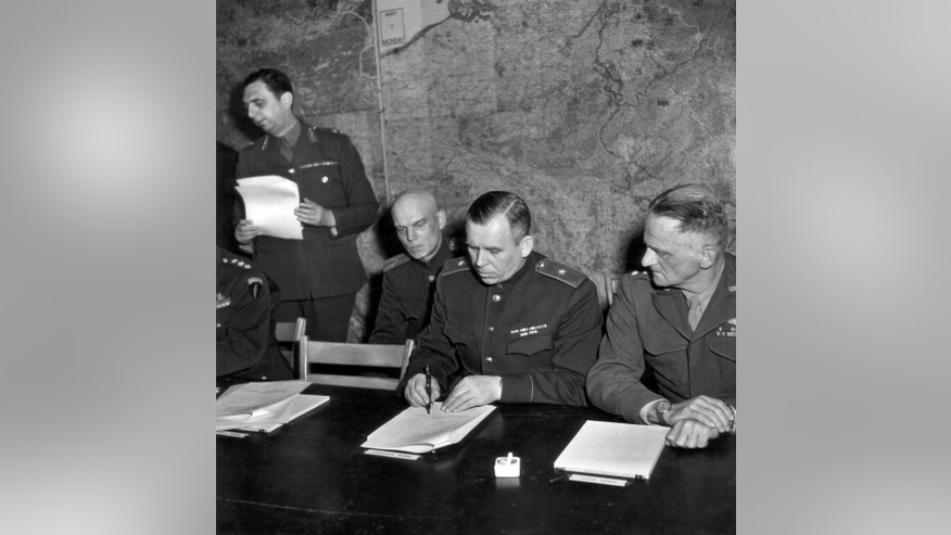 In this May 7, 1945 file photo, Gen. Ivan Susloparoff, Russian chief of staff, signs the unconditional surrender terms to Germany, negotiated at Reims, France. At left is his aide, Lt. Gen. Ivan Chermieff, and at right, Lt. Gen. C.A. Spaatz, USAAF. (Ralph Morse/Pool Photo via AP)