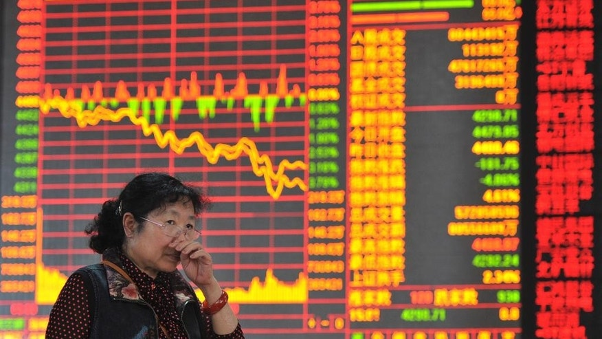 In this photo taken May 5, 2015, a Chinese woman rubs her nose near a display showing China's soaring stock index dip 4.06% at a brokerage house in Fuyang in central China's Anhui province. China's leaders are trying to tap the brakes on a stock market boom, reflecting fears that small investors were taking dangerous risks and a fall in prices could lead to political tensions or losses for the state-owned securities industry. (Chinatopix via AP) CHINA OUT