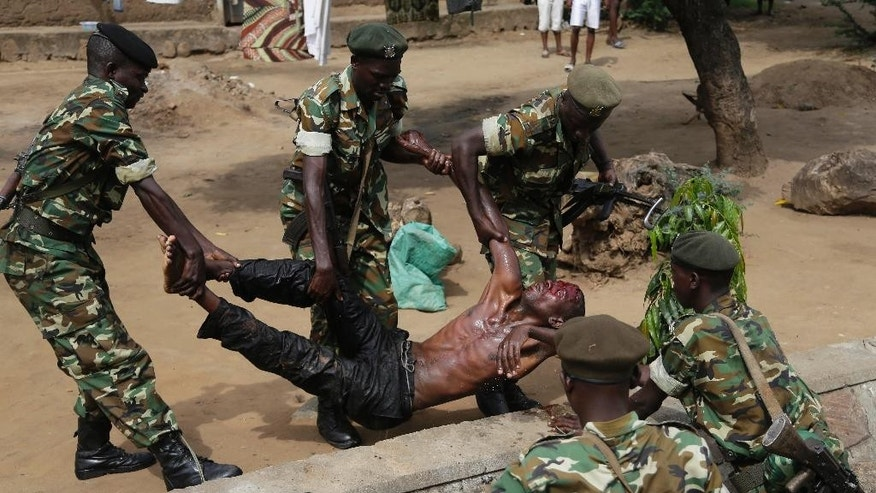 Soldiers lift a wounded suspected Imbonerakure militiaman who was attacked by demonstrators protesting against President Pierre Nkurunziza's decision to seek a third term in office in the Cibitoke district of Bujumbura, Burundi, Thursday May 7, 2015. They dispersed the crowd and retrieved the severely wounded man from a ditch he was thrown in.  At least one protestor has died in clashed with the widely feared Imbonerakure militias and police, sending scores to the streets seeking revenge. (AP Photo/Jerome Delay)