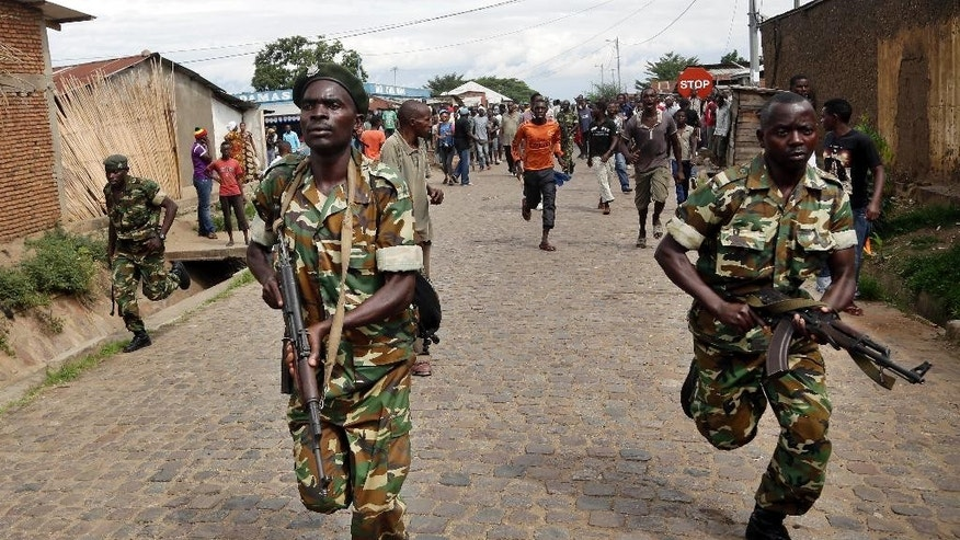 Soldiers run after demonstrators protesting President Pierre Nkurunziza's decision to seek a third term in office who caught and stoned a suspected Imbonerakure militiaman in the Cibitoke district of Bujumbura, Burundi, Thursday May 7, 2015. They dispersed the crowd and retrieved the severely wounded man from a ditch he was hiding in.  At least one protestor has died in clashed with the widely feared Imbonerakure militias and police, sending scores to the streets seeking revenge. (AP Photo/Jerome Delay)