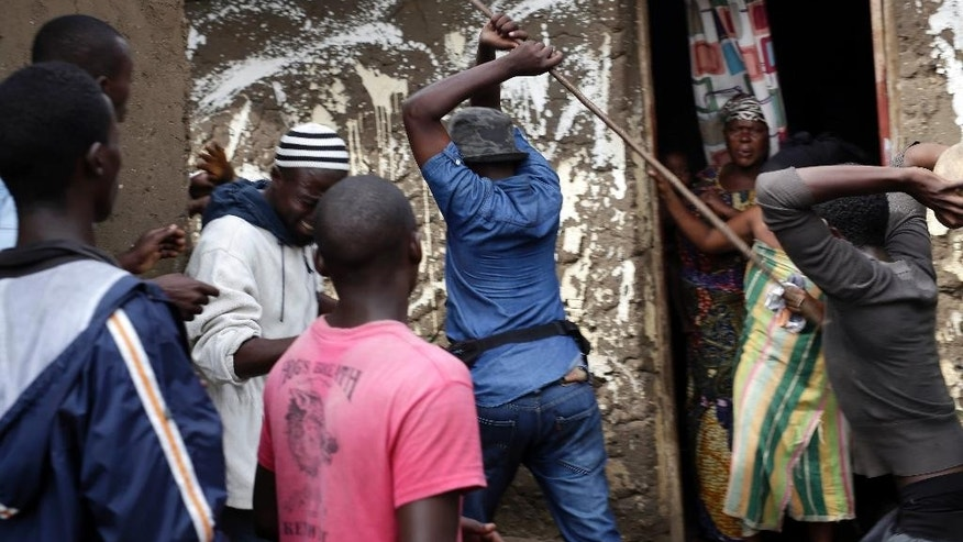 Demonstrators corner a suspected member of the ruling party's Imbonerakure youth militia at his home in the Cibitoke district of Bujumbura, Burundi, Thursday May 7, 2015. Jean Claude Niyonzima, a suspected member of the ruling party's Imbonerakure youth militia, fled from his house into a sewer under a hail of stones thrown by a mob protesting against President Pierre Nkurunziza's decision to seek a third term in office. He was later saved by soldiers. At least one protestor died in clashes with Imbonerakure militia and police. (AP Photo/Jerome Delay)