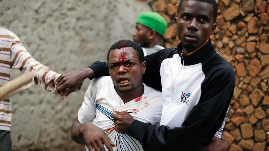 Jean Claude Niyonzima, a suspected member of the ruling party's Imbonerakure youth militia, is restrained as a mob gathers around his house, as protests continue against  President Pierre Nkurunziza's decision to seek a third term in office in the Cibitoke district of Bujumbura, Burundi, Thursday May 7, 2015. At least one protestor has died in clashed with the widely feared Imbonerakure militias and police, sending scores to the streets seeking revenge. This suspect eventually managed to flee under a hail of stones into a covered sewer, where he remained till the army fired shots into the air to disperse the crowd.(AP Photo/Jerome Delay)