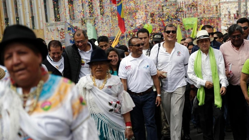 FILE - In this Friday, May 1, 2015, file photo, Ecuador's President Rafael Correa, third from the right, marches in the May Day parade in Quito, Ecuador. Ecuador's leader halted his motorcade when a 16-year-old appeared to make an obscene gesture at him, Correa got out and confronted the teenager. Officials say the boy was detained and later sentenced to 20 hours of community service for making offensive gestures at the president on May 1. (AP Photo/Dolores Ochoa, File)