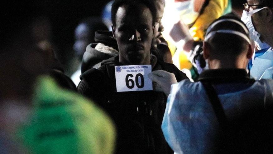Migrants have identification photos taken as they disembark from the Italian Financial Police ship Monte Cimone, that earlier rescued them at sea among nearly 100 others, at Catania's harbor, Sicily, southern Italy, Wednesday, May 6, 2015. The 98 migrants, a third of them women and three of them pregnant, were among hundreds of would-be refugees who arrived in Italian ports Wednesday after being rescued from overcrowded dinghies and fishing boats in recent days. (AP Photo/Antonio Calanni)