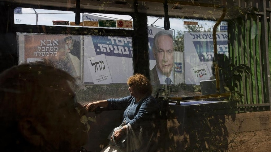 March 16, 2015: In this file photo, passengers sit in a bus driving past a billboard with the photo of Israeli Prime Minister Benjamin Netanyahu, right, and late rabbi Ovadia Yosef, a long time spiritual leader of the Shas party, a day ahead of legislative elections, in Bnei Brak near Tel Aviv, Israel.