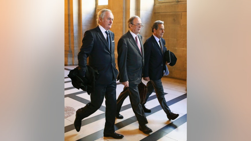Thierry Herzog's lawyers Philippe-Dehapiot, left, and Paul Albert Iweins, right, arrive with Nicolas Sarkozy' lawyer Pierre Haik, center, at Paris court house Thursday May 7, 2015 for the ruling on the facts that judges didn't break any laws when they wiretapped Nicolas Sarkozy in 2013-2014 . The Paris appeals court has ruled that investigating judges didn't break any laws when they tapped conversations between former President Nicolas Sarkozy and his lawyer Thierry Herzog, in connection with a probe into past campaign financing. (AP Photo/Remy de la Mauviniere)