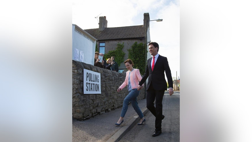 Labour Party leader Ed Miliband and his wife Justine  arrive at the polling station before voting at Sutton Village Hall, Doncaster, England, Thursday May 7, 2015, as Britain takes to the polls in a General Election. (AP Photo/Jon Super)