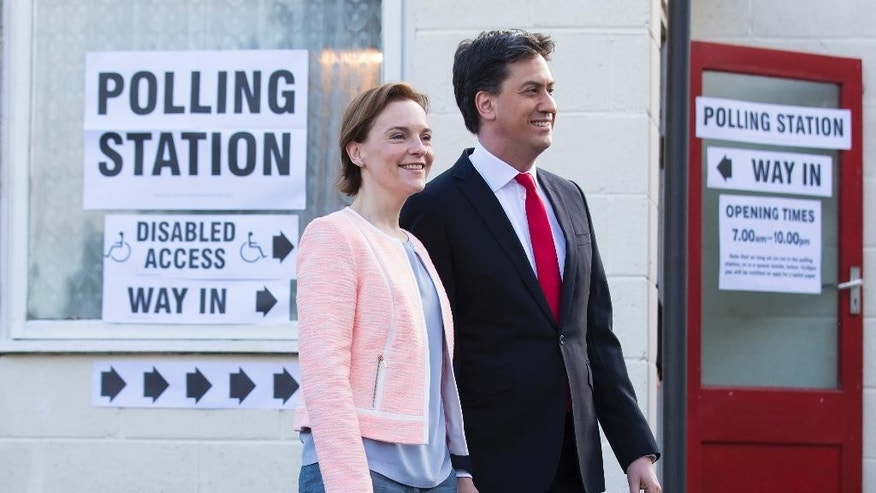Labour Party leader Ed Miliband and his wife Justine leave the polling station after voting at Sutton Village Hall, Doncaster, England, Thursday May 7, 2015. Polls have opened in Britain's national election, a contest that is expected to produce an ambiguous result, a period of frantic political horse-trading and a bout of national soul-searching.   (AP Photo/Jon Super)