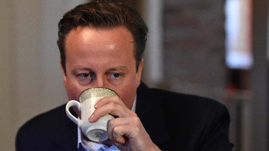 Britain's Prime Minister and leader of the Conservative Party, David Cameron enjoys a refreshing drink as he speaks with local members of the farming community during an election campaign visit at Whole House Farm, near Brecon, Wales,  Wednesday May 6, 2015. Britain's political candidates are campaigning all across Britain in search of votes ahead of the May 7 General Election. (Toby Melville/ Pool photo via AP)
