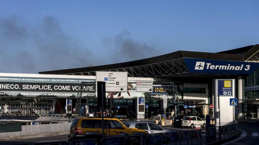 Smoke billows from Rome's Fiumicino airport main international terminal after a fire broke out overnight, Thursday, May 7, 2015. Italy's flagship Alitalia airline said in a statement that all departures have been canceled up to 2 p.m. (1200 GMT) and that only intercontinental flights will be allowed to land during that period.  The fire, which broke out after midnight, involved about 400 square meters (more than 4,000 square feet) of retail space. No cause was immediately identified. (Massimo Percossi/ANSA via AP)