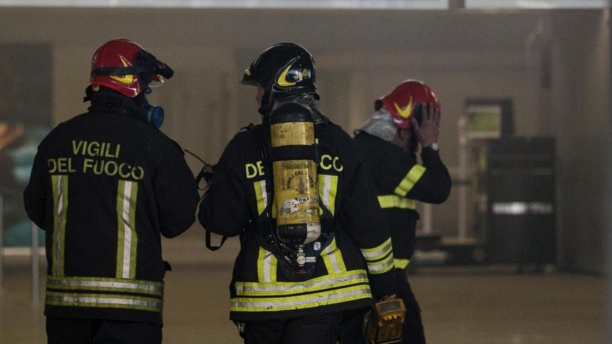 Firemen inspect Rome's Fiumicino airport main international terminal after a fire broke out overnight, Thursday, May 7, 2015. Italy's flagship Alitalia airline said in a statement that all departures have been canceled up to 2 p.m. (1200 GMT) and that only intercontinental flights will be allowed to land during that period.  The fire, which broke out after midnight, involved about 400 square meters (more than 4,000 square feet) of retail space. No cause was immediately identified. (Massimo Percossi/ANSA via AP)