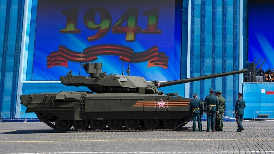 Russian army officers discuss a situation with a crew member of the new Russian T-14 Armata tank at the Red Square during a preparation for general rehearsal for the Victory Day military parade which will take place at Moscow's Red Square on May 9 to celebrate 70 years after the victory in WWII, in Moscow, Russia, Thursday, May 7, 2015.  One of the tanks moving on Red Square suddenly stopped while others drove away. The engine was still rumbling but it wouldn't move. After an attempt to tow it away the T-14 rolled away about 15 minutes later.(AP Photo/Alexander Zemlianichenko)