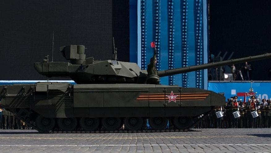 A crew member of new Russian T-14 Armata tank signals, that the tank has stopped in Red Square during a preparation for general rehearsal for the Victory Day military parade which will take place at Moscow's Red Square on May 9 to celebrate 70 years after the victory in WWII, in Moscow, Russia, Thursday, May 7, 2015.  One of the tanks moving on Red Square suddenly stopped while others drove away. The engine was still rumbling but it wouldn't move. After an attempt to tow it away the T-14 rolled away about 15 minutes later. (AP Photo/Alexander Zemlianichenko)