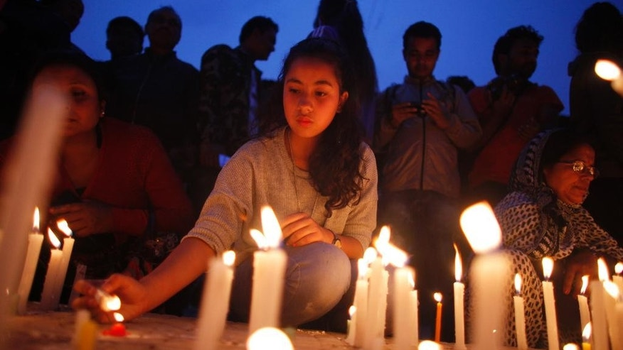 Nepalese people pay tributes to the victims of the April 25 earthquake, as they light candles near the destroyed landmark Dharahara tower in Kathmandu, Nepal, Thursday, May 7, 2015. The quake killed thousands and injured many more as it flattened mountain villages and destroyed buildings and archaeological sites in Kathmandu. (AP Photo/Niranjan Shrestha)