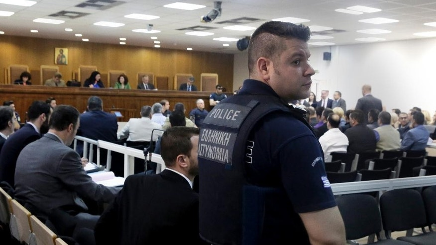 A Police officer looks on during a trial of dozens of members and volunteers of the far-right Golden Dawn party, at Korydallos, near Athens, Thursday, May 7, 2015. The trial of the leadership and dozens of members of Greece's extreme right Golden Dawn party has resumed, with the defendants facing charges of operating as a criminal organization that conducted a campaign of beatings and stabbings against migrants and left-wing opponents.  (AP Photo/Petros Giannakouris)