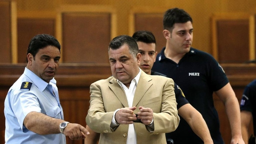 Police officers lead suspect Giorgos Roupakias at the start of a trial of dozens of members and volunteers of the far-right Golden Dawn party, at Korydallos, near Athens,  Thursday, May 7, 2015. The trial of the leadership and dozens of members of Greece's extreme right Golden Dawn party has resumed, with the defendants facing charges of operating as a criminal organization that conducted a campaign of beatings and stabbings against migrants and left-wing opponents.  (AP Photo/Petros Giannakouris)