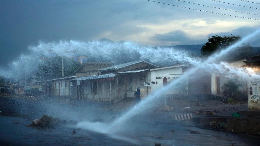A police officer keeps an eye on demonstrators as a water canon clears barricades in the Nyakabyga district of Bujumbura, Burundi, Friday, May 8, 2015. President Pierre Nkurunziza's officially filed to become a candidate for a potential third term in office. (AP Photo/Jerome Delay)