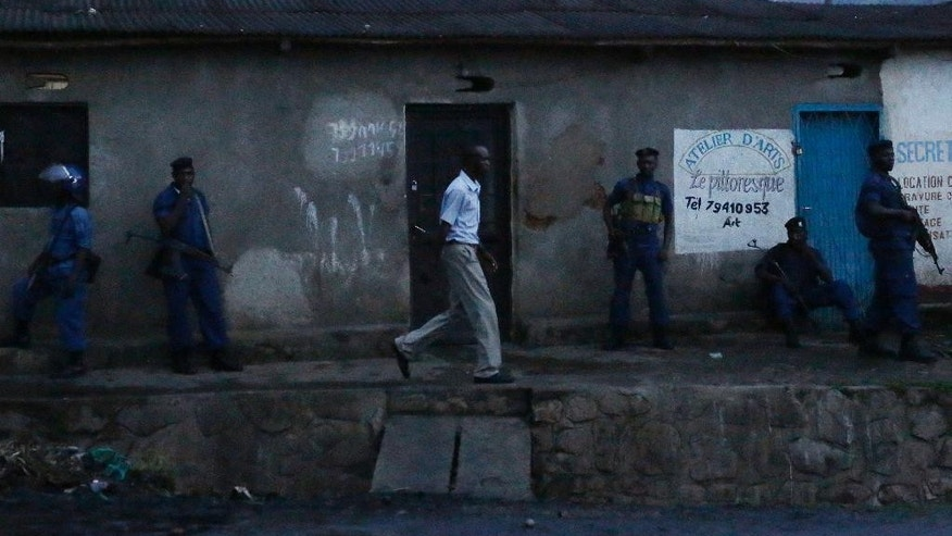A man walks past police securing bulldozers and water canons used to clear the barricades in the Nyakabyga district of Bujumbura, Burundi, Friday, May 8, 2015. President Pierre Nkurunziza's officially filed to become a candidate for a potential third term in office. (AP Photo/Jerome Delay)