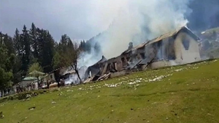 This still image taken from video shows smoke rising from an empty burning building, belonging to an army school, where a Pakistani army helicopter crashed in Nalter Valley, Gilgit,  Pakistan, Friday, May 8, 2015. The ambassadors to Pakistan from the Philippines and Norway and the wives of the ambassadors from Malaysia and Indonesia were killed Friday when a Pakistani army helicopter carrying foreign dignitaries made a crash landing in the country's north, the military said. (AP Photo)