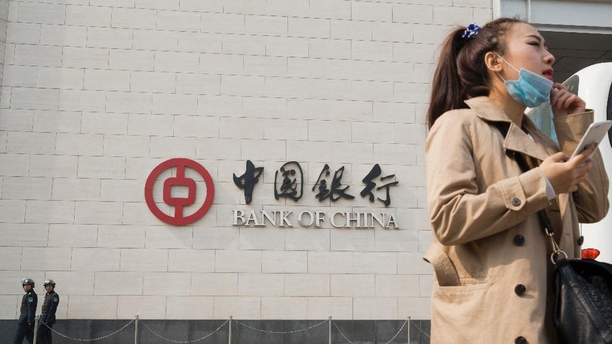 In this Saturday, March 7, 2015 photo, a woman waits in front of the headquarters of the Bank of China as security guards patrol the building in Beijing. At least three prominent Chinese banks, including the Bank of China, serve as safe havens for counterfeiters, who use them to process credit card payments for fakes or move their money around the globe, The Associated Press has found. (AP Photo/Ng Han Guan)