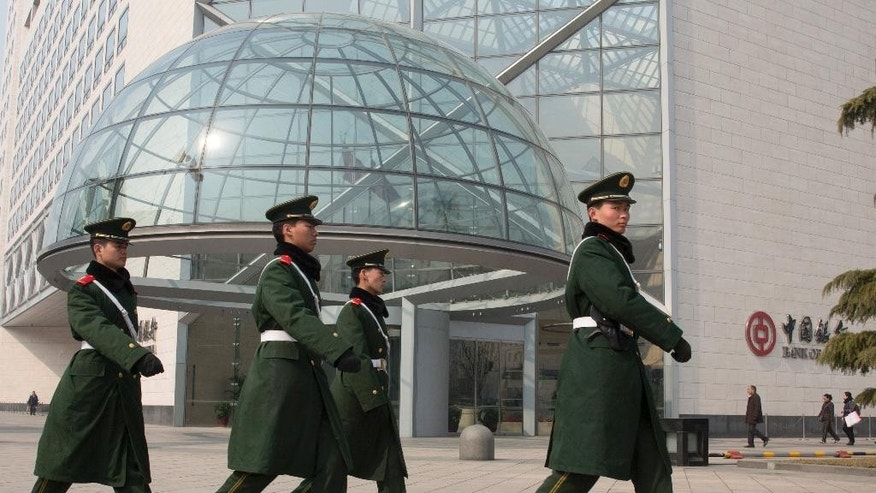 In this Saturday, March 7, 2015 photo, paramilitary police patrol near the headquarters of the Bank of China in Beijing. A review of hundreds of pages of court documents from cases in the United States and China, along with interviews with lawyers, investigators, government officials and industry representatives, show that a lack of legal cooperation between the West and China is allowing counterfeiters to use Chinese banks as financial shelters. (AP Photo/Ng Han Guan)