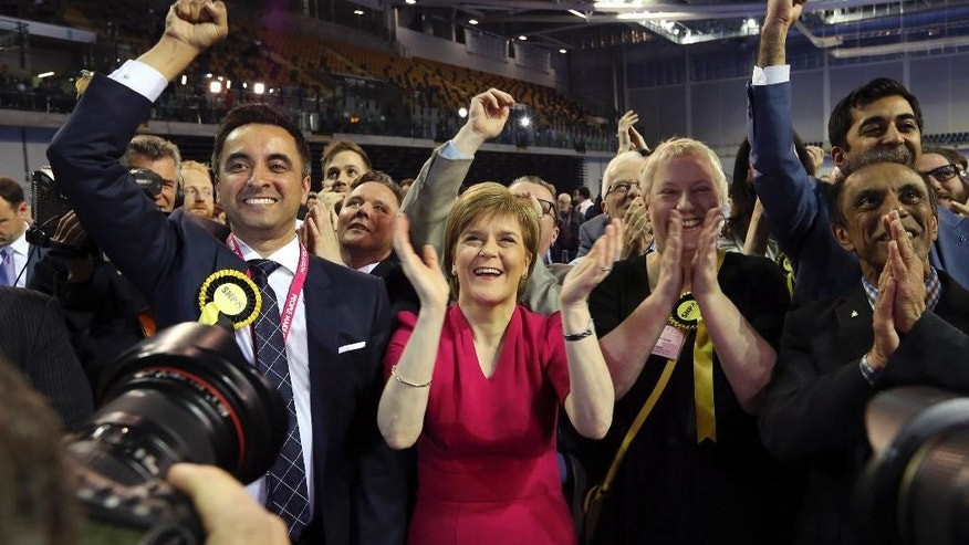 First Minister of Scotland and Scottish National Party leader Nicola Sturgeon, center, celebrates with the results for her party at the count of Glasgow constituencies for the general election in Glasgow, Scotland, Friday, May 8, 2015. The Conservative Party fared much better than expected in Britain's parliamentary election, with an exit poll and early returns suggesting that Prime Minister David Cameron would remain in his office at 10 Downing Street. The opposition Labour Party led by Ed Miliband took a beating, according to the exit poll, much of it due to the rise of the separatist Scottish National Party.  (AP Photo/Scott Heppell)