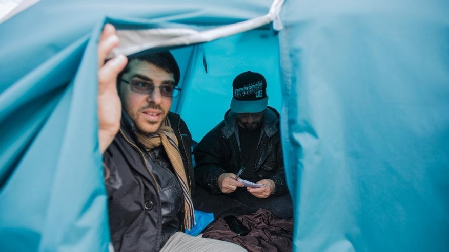 In this Wednesday, May 6, 2015 photo, freed Guantanamo Bay detainee Adel bin Muhammad El Ouerghi, of Tunisia, back, order his notes, as Omar Abdelahdi Faraj, from Syria, opens the tent in front of the U.S. embassy in Montevideo, Uruguay. The men are among six who were released from Guantanamo Bay, Cuba, after nearly 13 years in detention for alleged ties to al-Qaida. Uruguay's then-President Jose Mujica, a former leftist rebel who himself spent 13 years in prison in his homeland, invited them to resettle in this South American nation. (AP Photo/Matilde Campodonico)