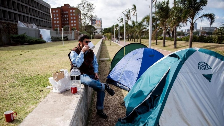 In this Wednesday, May 6, 2015 photo, freed Guantanamo Bay detainee Omar Abdelhadi Faraj, from Syria, sits and drinks tea in front of a tent outside the U.S. embassy as he protests along with fellow former detainees, in Montevideo, Uruguay.  Their grievances run the gamut, from demands that America compensate them to frustration over not being able to subscribe to Netflix in their adopted home. (AP Photo/Matilde Campodonico)