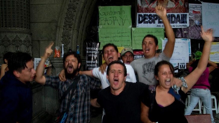 People celebrate after Guatemala's Vice President Roxana Baldetti resigned amid a customs corruption scandal that has implicated her former private secretary, in front of the National Palace in Guatemala City, Friday, May 8, 2015. President Otto Perez Molina announced on Friday that Baldetti will leave office. (AP Photo/Moises Castillo)