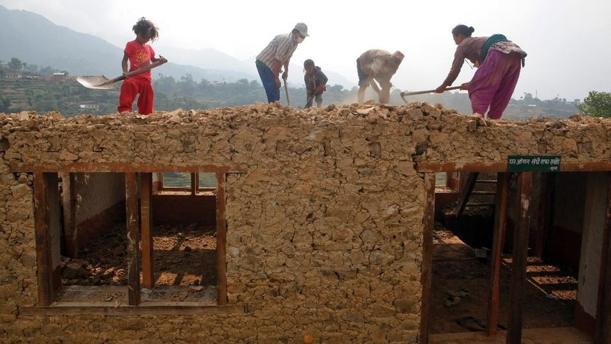 A Nepalese family works to rebuild their damaged house in Lalitpur, Nepal, Friday, May 8, 2015. The April 25 earthquake killed thousands and injured many more as it flattened mountain villages and destroyed buildings and archaeological sites in Kathmandu. (AP Photo/Niranjan Shrestha)