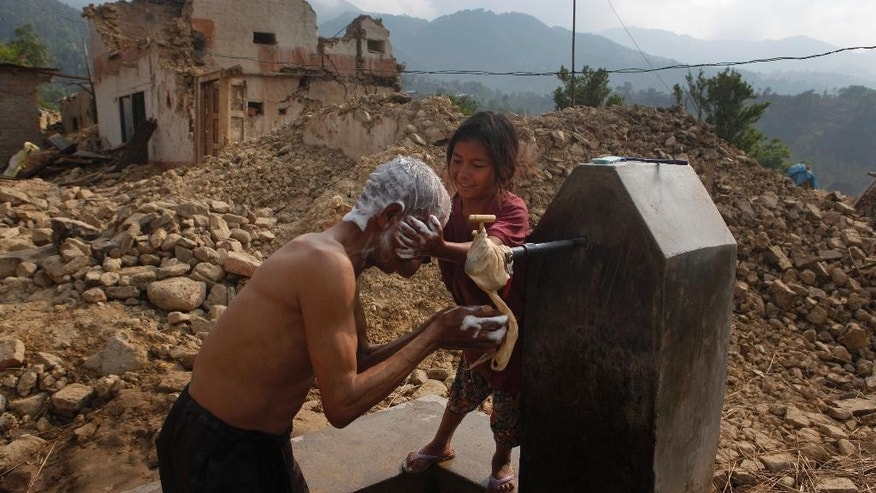 A child helps her grandfather take a wash outside their damaged home in Lalitpur, Nepal, Friday, May 8, 2015. The April 25 earthquake killed thousands and injured many more as it flattened mountain villages and destroyed buildings and archaeological sites in Kathmandu. (AP Photo/Niranjan Shrestha)