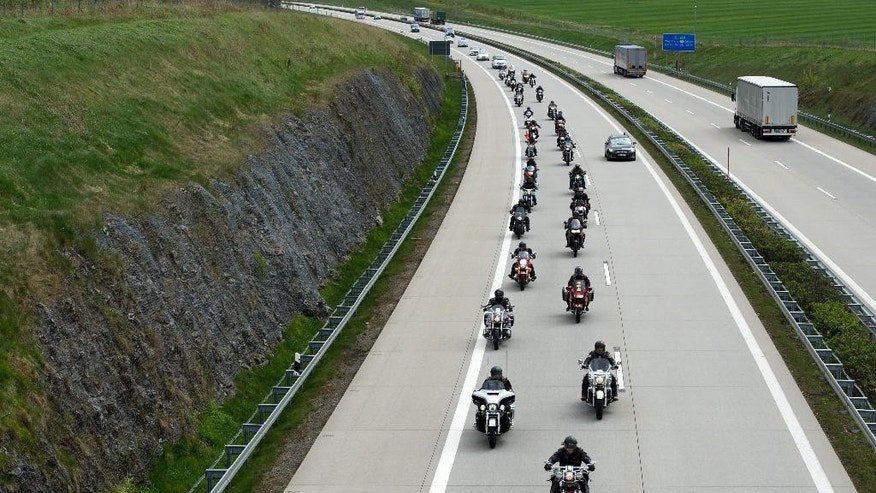 Members of the Russian motorcycle club 'Night wolves' as well as supporters ride their motorbikes along a motorway near Breitenau, Germany, May 7,2015. They are expected to arrive in Berlin on May 9, as part of their tour from Moscow to the German capital. Russia will celebrate the anniversary of the Soviet Union's World War II victory over Nazi Germany on the same day. ( Arno Burgi/dpa via AP)