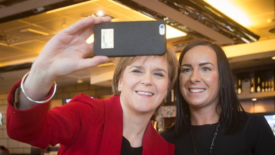 Scottish National Party leader Nicola Sturgeon, left,  stops for a selfie with a member of the public as she arrives at Edinburgh Airport before flying to London the day after Britain's General election Friday May 8, 2015. The SNP took 56 out of the 59 U.K. parliamentary seats in Scotland. Throughout Scotland, the vote for change and for a party that favors independence, was overwhelming. The SNP will now become the third largest party in the U.K. parliament (Danny Lawson/PA via AP) UNITED KINGDOM OUT