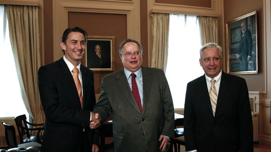 Amos Hochstein, left, U.S. State Department Special Envoy for International Energy Affairs, shakes hands with Greek Foreign Minister Nikos Kotzias, center, as U.S. Ambassador to Athens David D. Pearce, looks on, in Athens, Greece, on Friday, May 8, 2015. Hochstein is in Athens to hold talk with government officials over energy issues.  (AP Photo/Yorgos Karahalis)