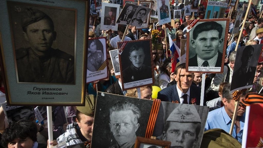 Local residents march as they carry portraits of relatives who fought in World War II, in central Moscow, Russia, Saturday, May 9, 2015. The march of the so-called Immortal Regiment is part of Saturday's commemoration of the 70th anniversary of victory over Nazi Germany. (AP Photo/Pavel Golovkin)