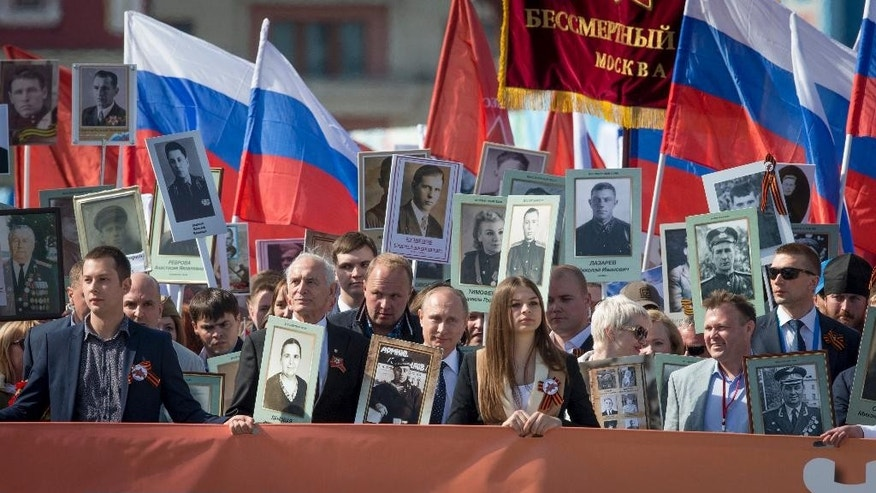 "Russian President Vladimir Putin, center, who joined the vast crowd as the first marchers reached Red Square, holds a photograph of his father in his naval uniform, as he walks with other people holding the banner reading ""Immortal Regiment"" and carrying portraits of relatives who fought in World War II through Red Square,  in Moscow, Russia, Saturday, May 9, 2015. The march of the so-called Immortal Regiment is part of Saturday's commemoration of the 70th anniversary of victory over Nazi Germany. (AP Photo/Ivan Sekretarev)"