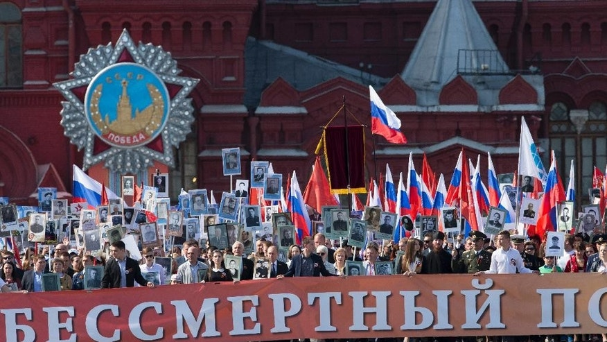 "Russian President Vladimir Putin, center, who joined the vast column as the first marchers reached Red Square, holds a photograph of his father in his naval uniform as he walks with other people holding the banner reading,  ""Immortal Regiment"" and portraits of relatives who fought in World War II through Red Square in Moscow, Russia, Saturday, May 9, 2015. The march of the so-called Immortal Regiment is part of Saturday's commemoration of the 70th anniversary of victory over Nazi Germany. (AP Photo/Ivan Sekretarev)"
