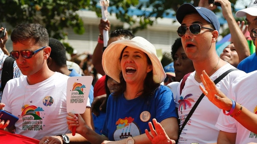 Mariela Castro, center, daughter of Cuba's President Raul Castro, takes part in a parade with Cuba's LGBT community in Havana, Cuba, Saturday, May 9, 2015. A day before Cuban President Raul Castro visits the Vatican, his daughter sponsored a blessing ceremony for gay couples on an island where gay marriage remains illegal. (AP Photo/Desmond Boylan)