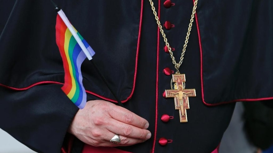Rev. Roger LaRade, of the Eucharistic Catholic Church in Canada, carries a gay pride flag before giving blessings to couples from the LGBT community in Havana, Cuba, Saturday, May 9, 2015. The blessing ceremony on an island where gay marriage remains illegal was part of official ceremonies leading up to the Global Day against Homophobia on May 17.  (AP Photo/Desmond Boylan)
