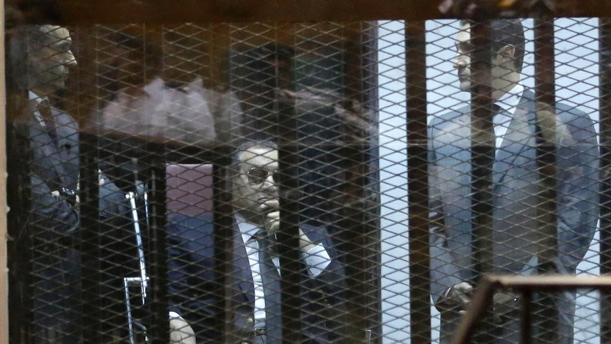 "Former Egyptian President Hosni Mubarak, seated, and his two sons Gamal Mubarak, left, and Alaa Mubarak, right, attend the verdict of the corruption case dubbed by the Egyptian media as the ""presidential palaces"" affair concerning charges that Mubarak and his two sons embezzled millions of dollars' worth of state funds over the course of a decade in a courtroom in Cairo, Egypt, Saturday, May 9, 2015. Egypt's deposed leader Hosni Mubarak and his two sons were sentenced Saturday to three years in prison and a fine in a retrial on corruption charges they faced earlier. It wasn't immediately clear whether it will include time he's already served since his country's 2011 revolt. (AP Photo/Hassan Ammar)"