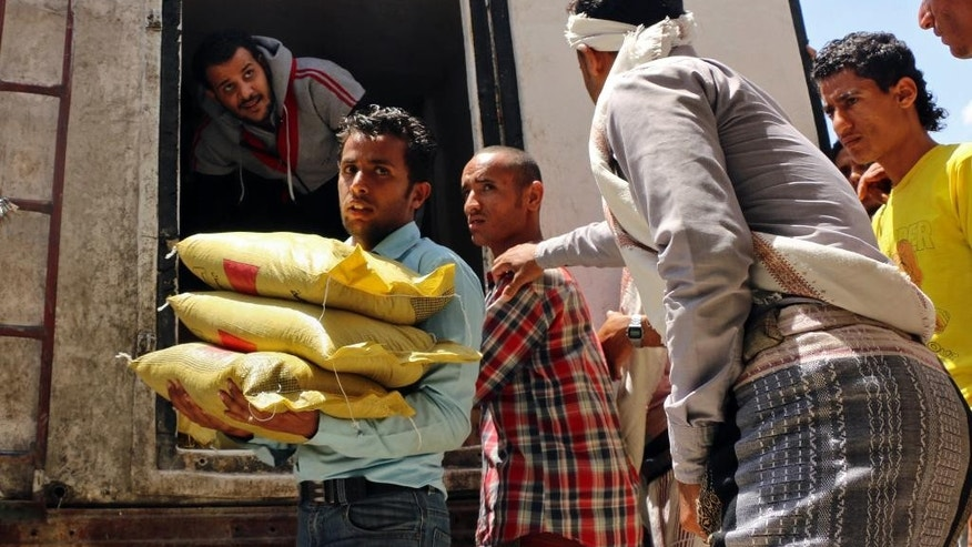 A Yemeni volunteer carries bags of rice to displaced people, who fled fighting in the southern city of Aden, during a food distribution effort by Yemeni volunteers, in Taiz, Yemen, Saturday, May 9, 2015. Humanitarian organizations say they face challenges delivering aid to citizens affected by the ongoing conflict, because of a severe fuel shortage and difficulty accessing warehouses. (AP Photo/Abdulnasser Alseddik)
