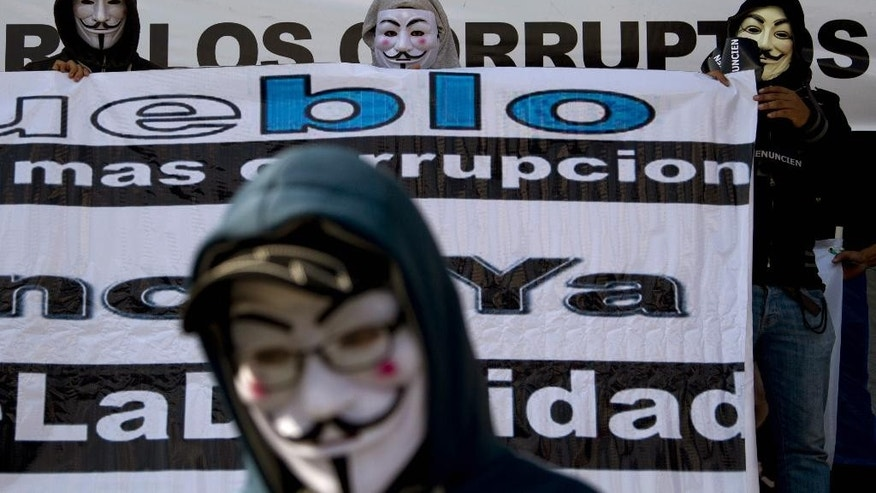 Masked protesters demand the resignation of Guatemalan President Otto Perez Molina outside the National Palace in Guatemala City, Saturday, May 9, 2015. Perez Molina's Vice President Roxana Baldetti resigned on Friday amid a customs corruption scandal that has implicated her former private secretary. (AP Photo/Moises Castillo)